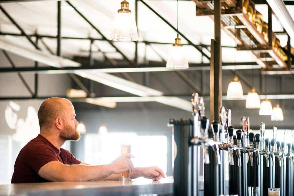 A man drinking craft beer at the bar.
